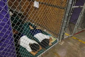 NOGALES, AZ - JUNE 18:  Two female detainees sleep in a holding cell, as the children are separated by age group and gender, as hundreds of mostly Central American immigrant children are being processed and held at the U.S. Customs and Border Protection Nogales Placement Center on June 18, 2014, in Nogales, Arizona.  Brownsville, Texas, and Nogales, have been central to processing the more than 47,000 unaccompanied children who have entered the country illegally since Oct. 1. (Photo by Ross D. Franklin-Pool/Getty Images)