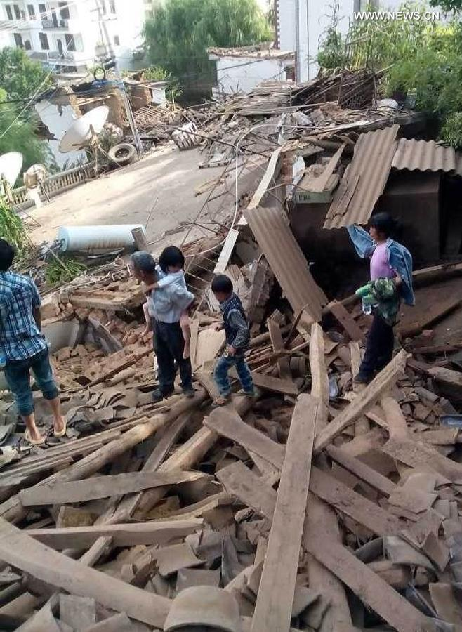 Survivors survey the rubble. Picture courtesy of Xinhua News.