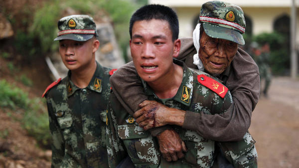 A paramilitary police officer carries an elderly man on his back after an earthquake hit Yunnan province China on Aug. 3. Picture courtesy of The Chicago Tribune